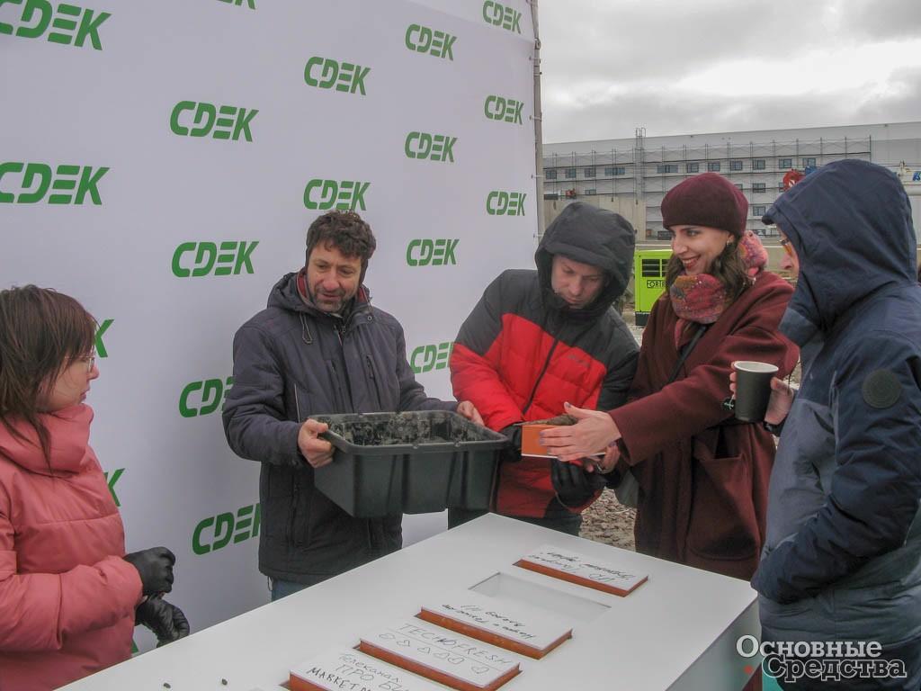 Журналисты закладывают первые камни в основание нового склада